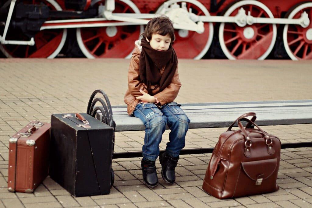 En gutt som sitter på togstasjonen med tre kofferter og skal flytte